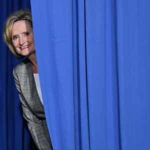 Senator Cindy Hyde-Smith peaks out from behind a curtain before a rally with US President Donald Trump at  Landers Center Ð Arena in Southaven, Mississippi, on October 2, 2018. (Photo by MANDEL NGAN / AFP)        (Photo credit should read MANDEL NGAN/AFP/Getty Images)