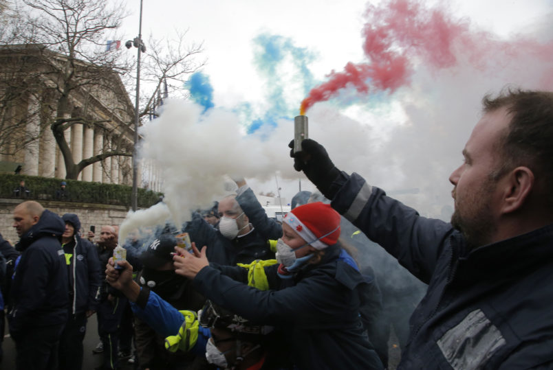 Ambulance workers hold flares outside the National Assembly in Paris Monday Dec. 3 2018. Ambulance workers took to the streets and gathered close to the National Assembly in downtown Paris to complain about changes to working conditions as French Prime