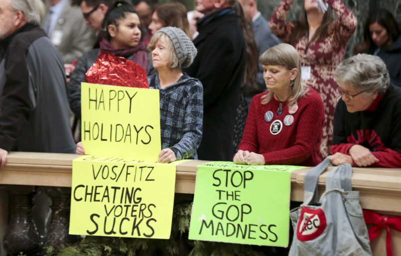 Protesters Peppi Elder, left, and Christine Taylor during the lighting of the 2018 State Capitol Christmas Tree in the Wisconsin State Capitol Rotunda. The Senate and Assembly are set to send dozens of changes in state law to Gov. Scott Walker's desk Tuesday Dec. 4, 2018 at the Capitol in Madison. (AP Photo/Wisconsin State Journal, Steve Apps)