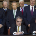 "Acting EPA Administrator Andrew Wheeler, seated left, signs an order withdrawing federal protections for countless waterways and wetlands, as Assistant Secretary of the Army for Civil Works Rickey ""RD"" James, seated right, looks on, at EPA headquarters in Washington, Tuesday, Dec. 11, 2018. Look on behind are Senate Agriculture Committe Chairman Pat Ross, R-Kansas, left, and Secretary of the Interior Ryan Zinke, second from right.   (AP Photo/Cliff Owen)"