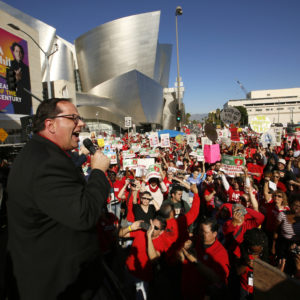 United Teachers Los Angeles president, Alex Caputo-Pearl addresses thousands of teachers who may go on strike against the nation's second-largest school district next month, as they rally next to the Walt Disney Concert Hall downtown Los Angeles Saturday, Dec. 15, 2018. The union contends that the district is hoarding a huge financial reserve that could be used to pay teachers more and improve conditions for students. Union leaders also criticized a plan to reorganize the district by dividing it into 32 networks. Saturday's march ended at the Broad Museum to highlight the role billionaires like Eli Broad have by funding the corporate charter industry and privatization efforts. (AP Photo/Damian Dovarganes)