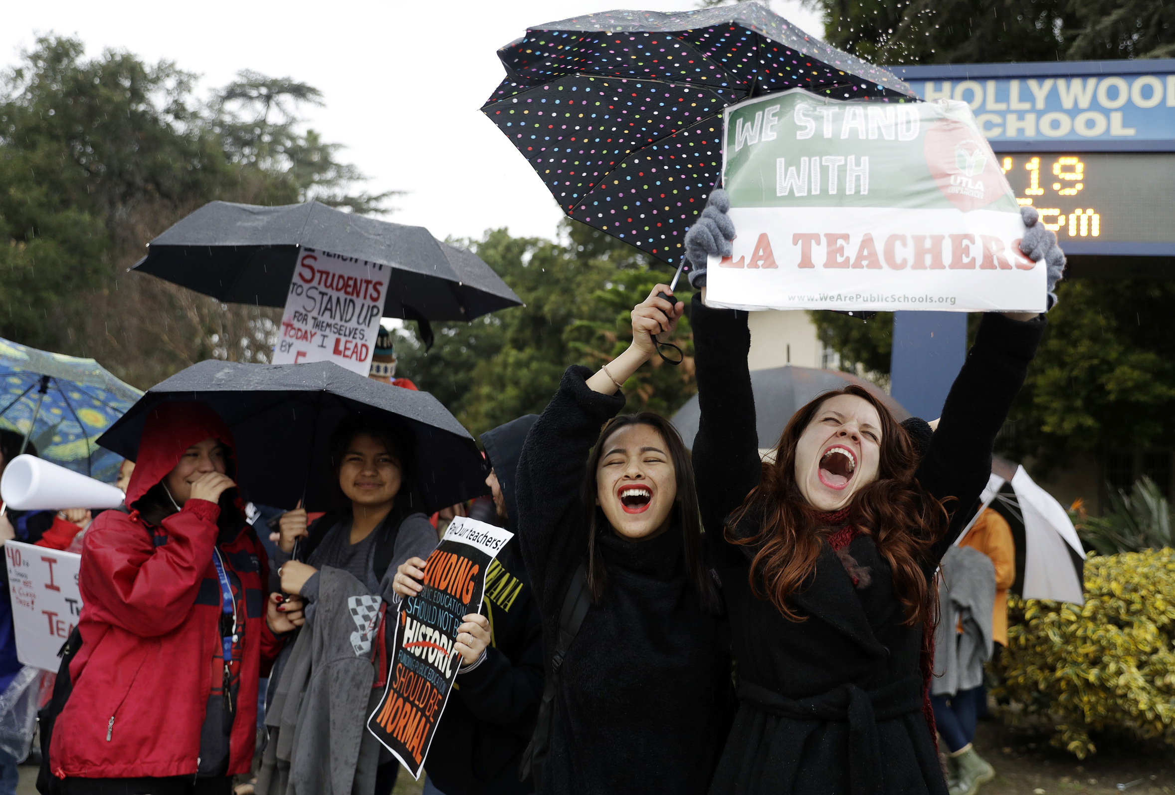Maria Arienza, right, an English and Spanish teacher, shouts slogans alongside her student Stephanie Medrano, second from right, outside of North Hollywood High School Tuesday, Jan. 15, 2019, in Los Angeles. Teachers in the huge Los Angeles Unified School District walked picket lines again Tuesday as administrators urged them to return to classrooms and for their union to return to the bargaining table. (AP Photo/Marcio Jose Sanchez)