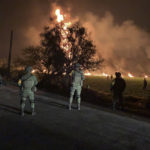 In this image provided by the Secretary of National Defense, soldiers guard the area where the explosion was recorded in Tlahuelilpan, Hidalgo state, Mexico, Friday, Jan. 18, 2019. A huge fire exploded at a pipeline leaking fuel in central Mexico on Friday, killing at least 21 people and badly burning 71 others as locals were collecting the spilling gasoline in buckets and garbage cans, officials said.The leak was caused by an illegal tap that fuel thieves had drilled into the pipeline in a small town in the state of Hidalgo, about 62 miles (100 kilometers) north of Mexico City, according to state oil company Petroleos Mexicanos, or Pemex. (Secretary of National Defense via AP)