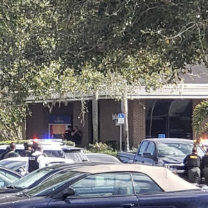 Law enforcement officials take cover outside the SunTrust Bank branch, Wednesday, Jan. 23, 2019, in Sebring, Fla. Authorities say they've arrested a man who fired shots inside the Florida bank. (Highlands NewsSun via AP)