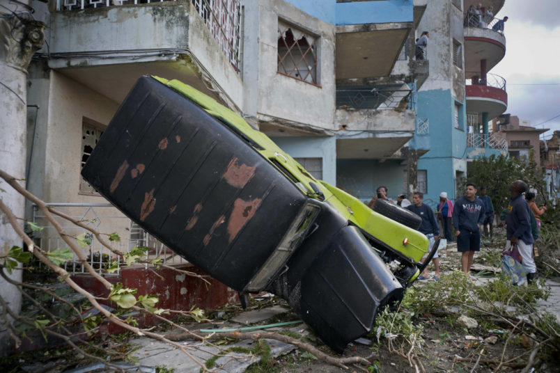 People walk next to a car overturned by the force of the tornado in Havana, Cuba, Monday, Jan. 28, 2019. A tornado and pounding rains smashed into the eastern part of Cuba's capital overnight, toppling trees, bending power poles and flinging shards of metal roofing through the air as the storm cut a path of destruction across eastern Habana.Power was cut to many areas and President Miguel Diaz-Canel said Monday at least three people were killed and 172 injured. (AP Photo/Ramon Espinosa)
