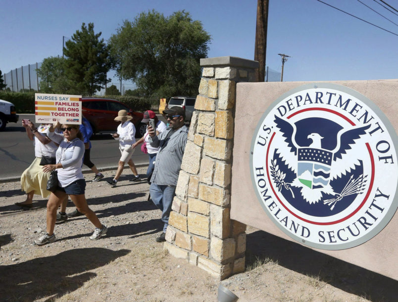 File-This June 2018, file photo shows protesters walking along Montana Avenue outside the El Paso Processing Center, in El Paso, Texas. Federal immigration officials are force feeding some of the dozens of Cuban and Indian immigrants who have been on hunger strike for nearly a month inside a Texas detention facility, The Associated Press has learned.  (Rudy Gutierrez/The El Paso Times via AP, File)