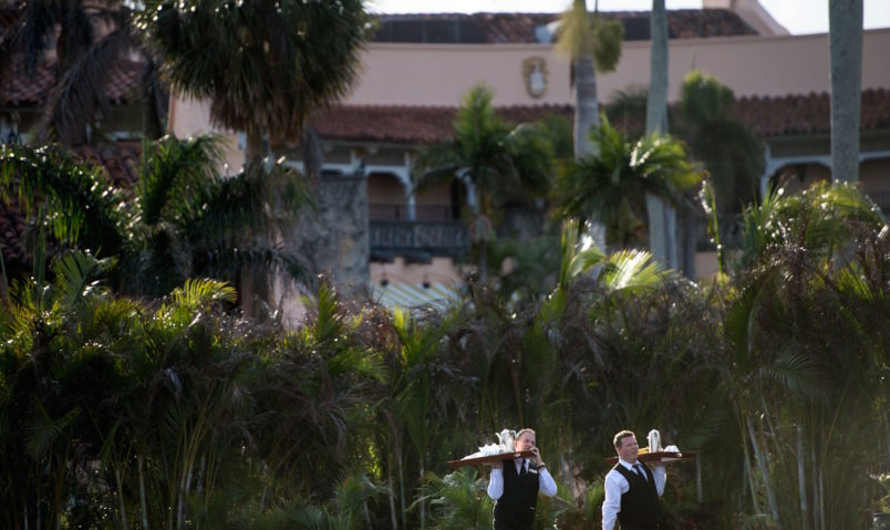 Staff carry trays of coffee at Mar-a-Lago while US President Donald Trump visits his property March 24, 2018 in Palm Beach, Florida. / AFP PHOTO / Brendan Smialowski (Photo credit should read BRENDAN SMIALOWSKI/AFP/Getty Images)