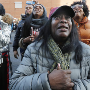 Cahana Yehudah, foreground, of the Bronx, cries as she hears the response of prisoners held inside the Metropolitan Detention Center, a federal facility with all security levels, Sunday, Feb. 3, 2019, in the Brooklyn borough of New York. The prison has been without heat, hot water, electricity and good sanitation for several days, including during the recent frigid weather. Yehudah has a brother who is serving 18 months at the prison for gun possession. (AP Photo/Kathy Willens)