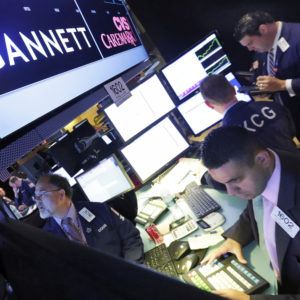 FILE - In this Aug. 5, 2014, file photo, specialist Michael Cacace, foreground right, works at the post that handles Gannett on the floor of the New York Stock Exchange.  Gannett is walking away from its takeover attempt at Tronc, the publisher of the Los Angeles Times, Chicago Tribune and other major dailies. Shares of Gannett Co., publisher of USA Today, are surging more than 8 percent in premarket trading Tuesday, Nov. 1, 2016.  (AP Photo/Richard Drew, File)