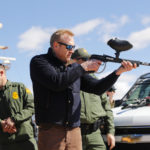 Acting Secretary of Defense Patrick Shanahan, center, fires a modified painted ball gun during a tour of the US-Mexico border at Santa Teresa Station in Sunland Park, N.M., Saturday, Feb. 23, 2019. (AP Photo/Pablo Martinez Monsivais)