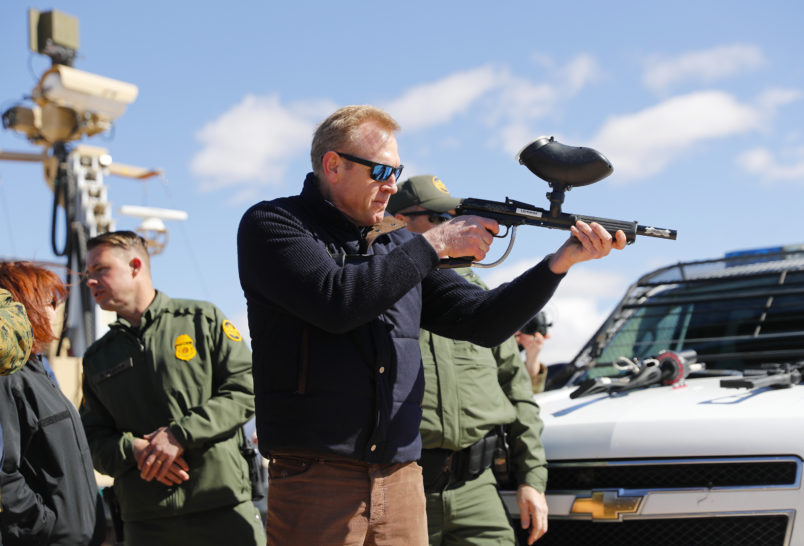 Acting Secretary of Defense Patrick Shanahan, center, fires a modified painted ball gun during a tour of the US-Mexico border at Santa Teresa Station in Sunland Park, N.M., Saturday, Feb. 23, 2019. (AP Photo/Pablo Martinez Monsivais)