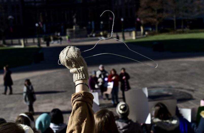 OHIO STATE HOUSE, COLUMBUS, OHIO, UNITED STATES - 2018/12/12: A protester seen holding a coat hanger which is an emblem of the pro-choice movement during a protest against the controversial Heartbeat Bill or HB258, which bans abortion once a fetal heartbeat is detected. The bill would make it much more difficult for women to seek an abortion in the state of Ohio. The bill was passed by members of the Ohio Senate with a vote of 18-13. Outgoing Ohio Governor John Kasich has said he would veto any such bill should it be passed by the Senate. (Photo by Matthew Hatcher/SOPA Images/LightRocket via Getty Images)