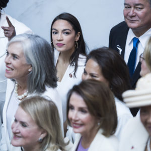 "UNITED STATES - FEBRUARY 05: Rep. Alexandria Ocasio-Cortez, D-N.Y., top center, and Speaker Nancy Pelosi, D-Calif., bottom center, pose for a group photo of House Democrats in the Capitol Visitor Center, who plan to wear ""suffragette white"" to the State of the Union address to show solidarity for women's agendas on Tuesday, February 5, 2019. (Photo By Tom Williams/CQ Roll Call)"